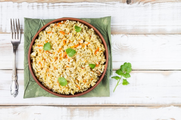 Contorno vegetariano stufato di riso integrale con cipolle, carote e sedano in una ciotola su una luce
