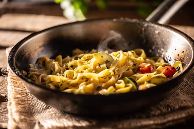 Tagliatelle vegetariane con zucchine e pomodori servite in una padella bollente.