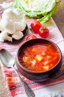 Zuppa di pomodoro vegetariana con cavolo e cavolfiore in una ciotola rustica in ceramica