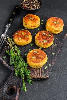 Tortino di hamburger vegetariani vegani con verdure ed erbe aromatiche. sfondo nero. vista dall'alto.