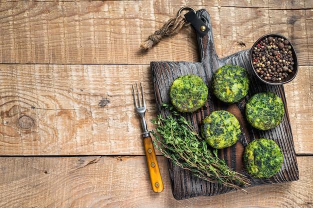 Tortino di hamburger vegetali vegetariani con erbe su tavola di legno. fondo in legno. vista dall'alto. copia spazio.