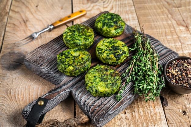 Tortino di hamburger vegetali vegetariani con erbe su tavola di legno. fondo in legno. vista dall'alto.