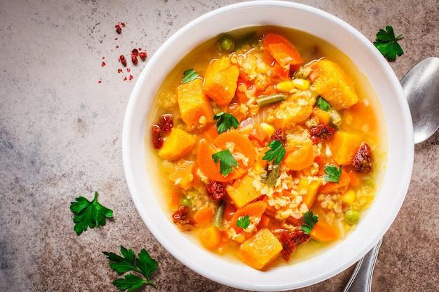 Zuppa di verdure vegetariana con lenticchie e zucca in zolla bianca