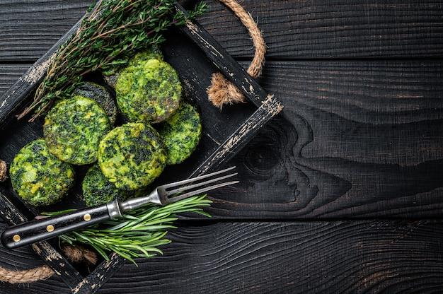 Tortino di falafel vegetale vegetariano con erbe in un vassoio di legno. sfondo nero. vista dall'alto. copia spazio.