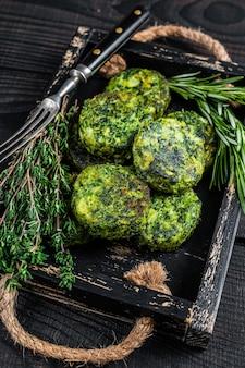 Tortino di falafel vegetale vegetariano con erbe in un vassoio di legno. sfondo nero. vista dall'alto.
