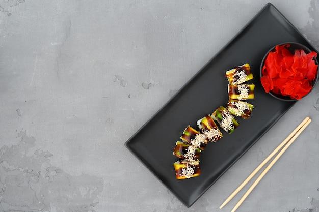 Rotolo di sushi vegetariano con verdure su sfondo grigio vista dall'alto