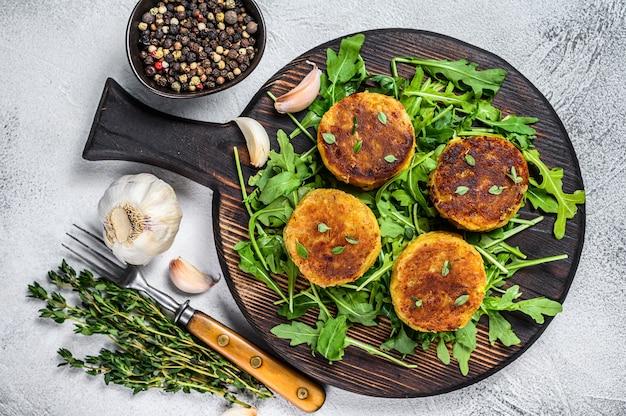 Cotoletta di tortino vegetariano con lenticchie, verdure e rucola. sfondo bianco. vista dall'alto.