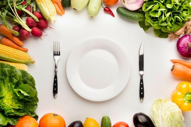 Cornice di verdure con piatto vuoto