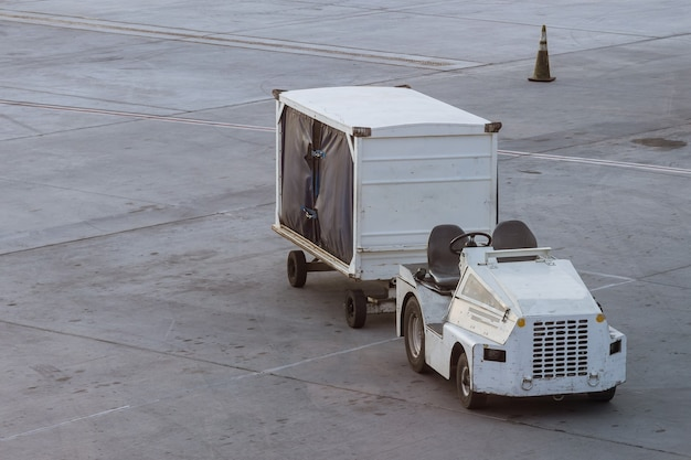 Veicolo per carico in attesa per il trasporto in aereo sulla pista dell'aeroporto