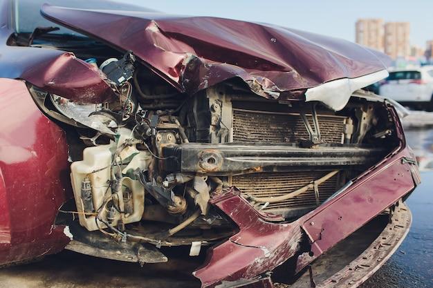 Veicolo che mostra un danno alla parte anteriore che termina con un altro veicolo a una luce rossa.