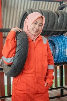 Meccanica donna velata indossa un'uniforme wearpack quando trasporta un pneumatico per motocicletta mentre si trova in un'officina di riparazione di motociclette
