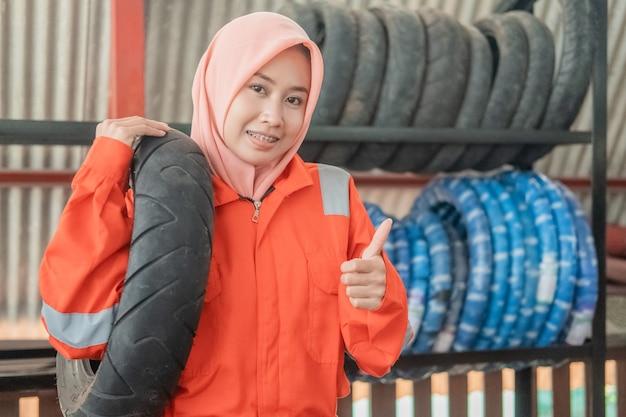 Il meccanico femminile velato indossa un'uniforme wearpack con il pollice in alto quando trasporta un pneumatico per motocicletta mentre è in un'officina di riparazione di motociclette