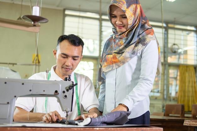 Il supervisore velato sta a vegliare sui dipendenti che lavorano alle macchine da cucire