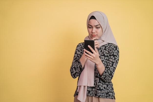 Donna velata che guarda lo schermo mentre usa uno smartphone con espressione preoccupata con copyspace