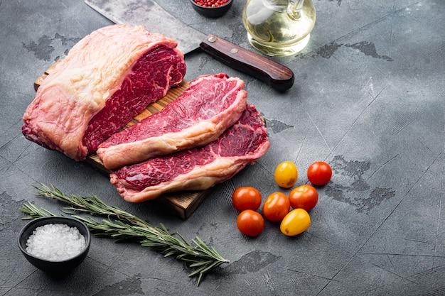 Bistecca venosa, carne cruda di manzo marmorizzata, sul tavolo grigio,