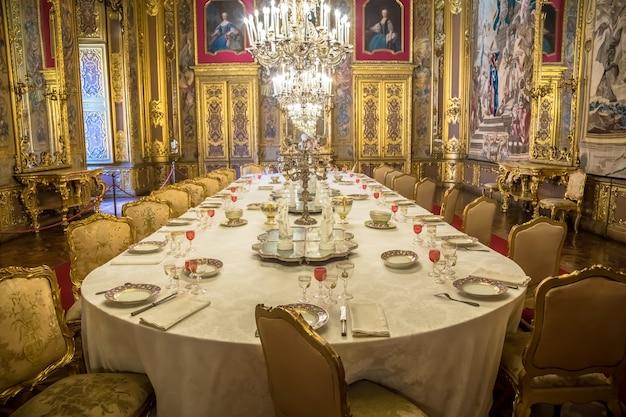Venaria reale, italia - circa agosto 2020: lussuosa sala da pranzo in stile barocco con tavola per cena di gala