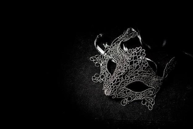 Maschera veneziana da donna nera, sola su superficie nera. concetto di mistero romantico