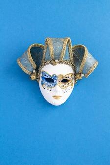 Maschera di carnevale veneziano al centro dello sfondo blu. posizione verticale vista dall'alto. copia spazio.