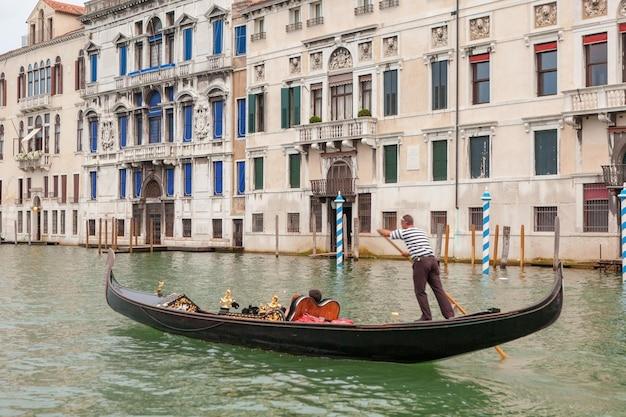 Gondoliere veneziano punting gondola attraverso le verdi acque del canale di venezia, italia