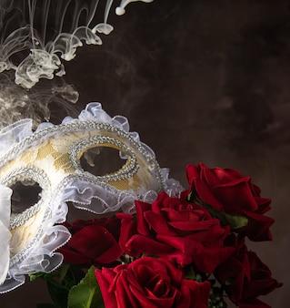 Maschera veneziana, rose e fumo in belle forme, messa a fuoco selettiva.