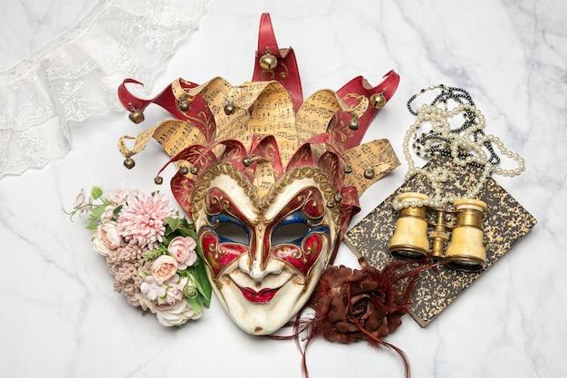 Maschera veneziana con un libro e un binocolo da teatro su un tavolo di marmo