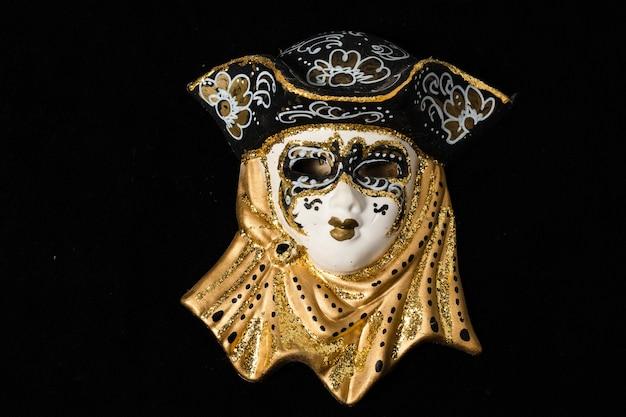 Maschere veneziane di ornamento in ceramica bianca e nera con riflessi dorati o dorati. sfondo nero.