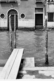 Vista veneziana con canale e piccolo molo, venezia, italia. bianco e nero
