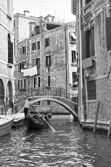 Vista veneziana con piccolo canale e gondola, venezia, italia. bianco e nero