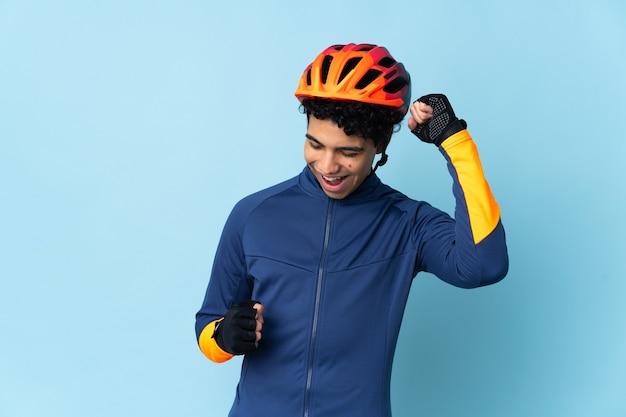 Uomo venezuelano ciclista isolato su sfondo blu che celebra una vittoria