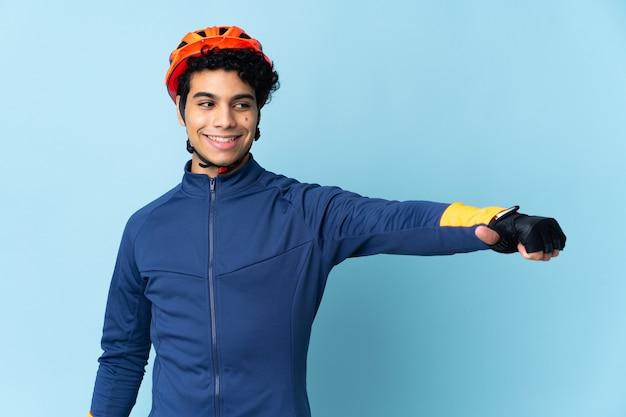 Uomo venezuelano ciclista isolato su sfondo blu che dà un pollice in alto gesto