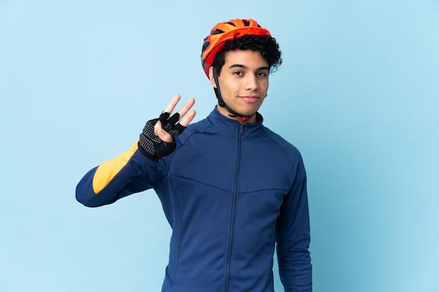 Uomo venezuelano ciclista isolato su sfondo blu felice e contando tre con le dita