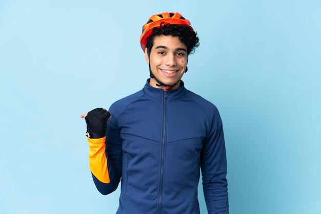 Uomo venezuelano ciclista isolato su sfondo blu che punta di lato per presentare un prodotto