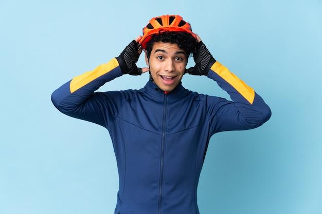 Uomo venezuelano ciclista isolato su sfondo blu con espressione di sorpresa