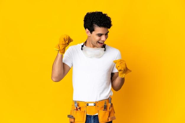 Elettricista venezuelano uomo isolato su sfondo giallo che celebra una vittoria