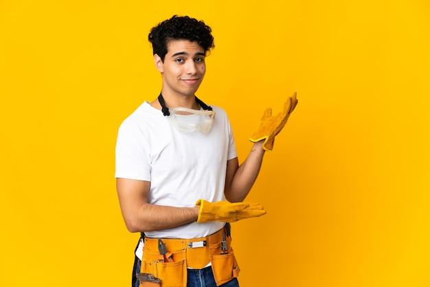 Elettricista venezuelano uomo isolato su sfondo giallo che estende le mani di lato per invitare a venire