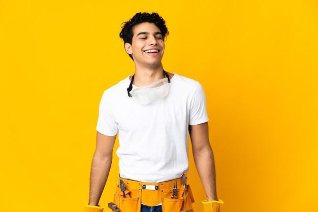 Elettricista venezuelano uomo isolato su sfondo giallo ridendo