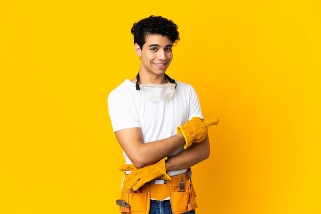 Elettricista venezuelano uomo isolato su sfondo giallo che punta il dito di lato