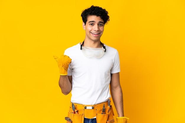 Elettricista venezuelano uomo isolato su sfondo giallo che punta di lato per presentare un prodotto
