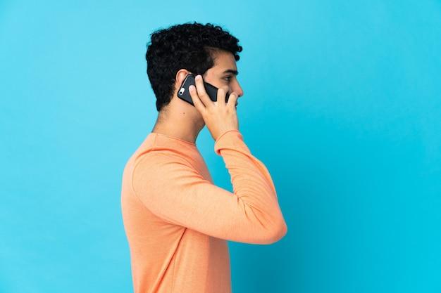 Uomo venezuelano isolato sull'azzurro mantenendo una conversazione con il telefono cellulare con qualcuno