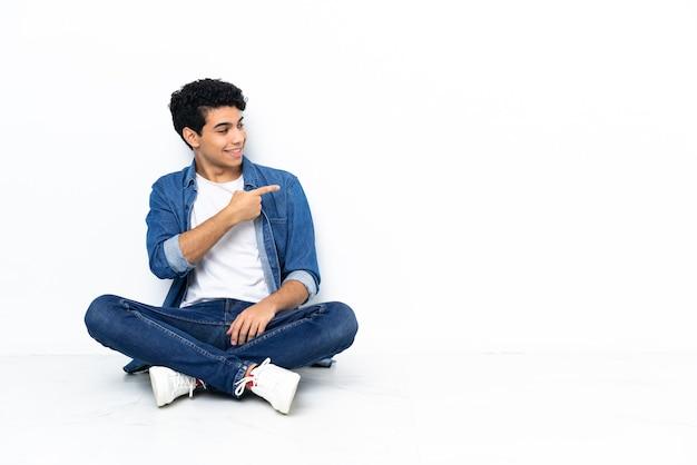 Uomo venezuelano seduto sul pavimento che punta il dito di lato