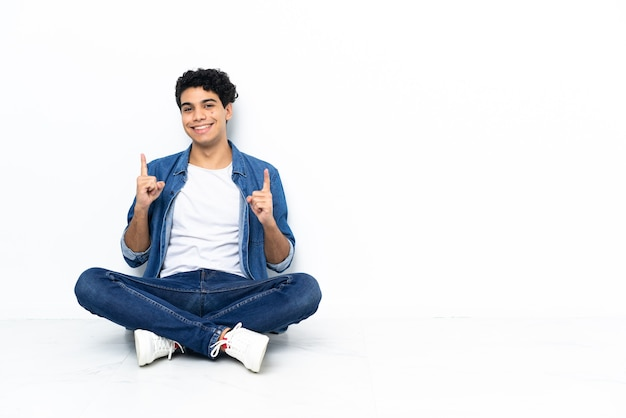 Uomo venezuelano seduto sul pavimento che indica una grande idea