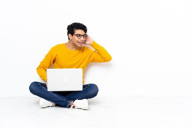 Uomo venezuelano seduto sul pavimento con il computer portatile che ascolta qualcosa mettendo la mano sull'orecchio
