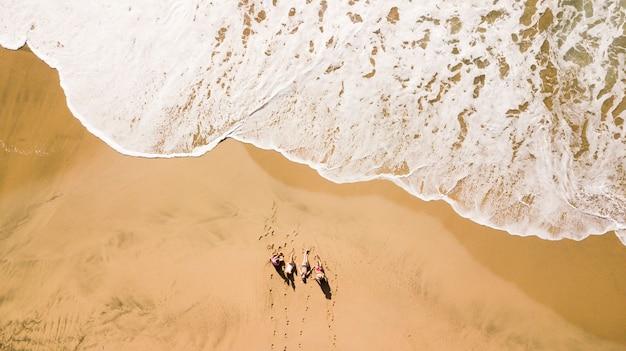 Veduta aerea verticale di un gruppo di amici giovani che godono le vacanze di vacanza estiva in spiaggia con la grande onda in arrivo