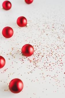Sfondo verticale con palle di natale rosse e glitter colorati a forma di stella