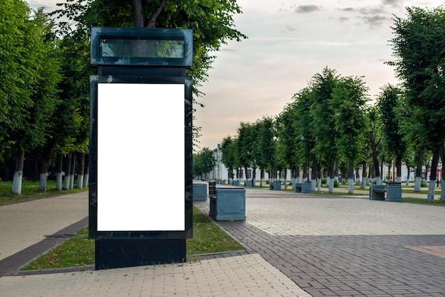 Tabellone per le affissioni nero verticale con spazio. mockup con uno sfondo bianco, per la pubblicità. parco mattutino senza persone e con alberi verdi.