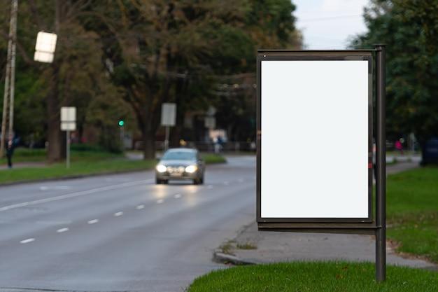 Tabellone per le affissioni in bianco verticale sulla via della città, in superficie la strada di sera defocused con le automobili