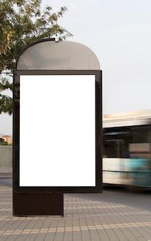 Tabellone per le affissioni verticale vuoto sulla strada della città con bus