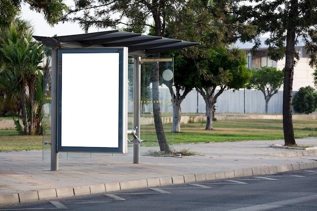 Tabellone per le affissioni in bianco verticale sulla via della città con gli alberi verdi