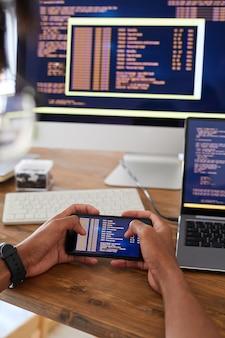 Primo piano verticale delle mani maschii che tengono smartphone con codice sullo schermo mentre si lavora alla scrivania in ufficio, concetto di sviluppatore it, copia dello spazio