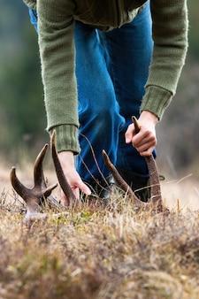 Composizione verticale un antler di cervo capannone raccolta umana nella natura primaverile